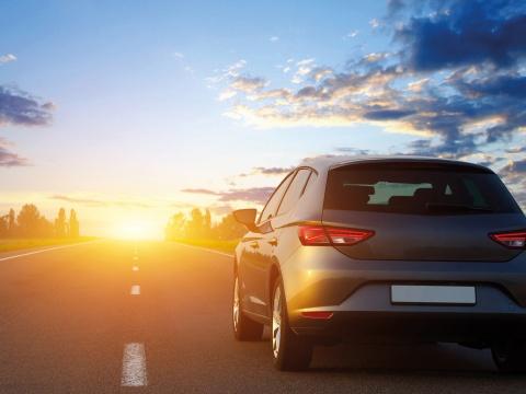 Car driving towards sunset